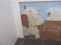 This is long term water damage from a leaking shower. The tiles have come loose and the wall render needed repairing.
